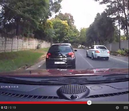 Dashboard camera captures driver of BMW overtaking on solid white line in residential area