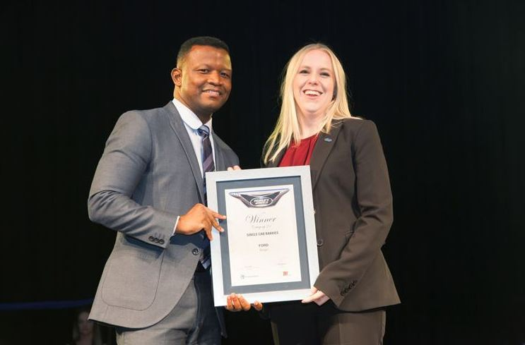 Tracey Delate, General Marketing Manager, Ford Motor Company of Southern Africa receives one of four Ford awards from Nicholas Nkosi, Head of Retail Banking...