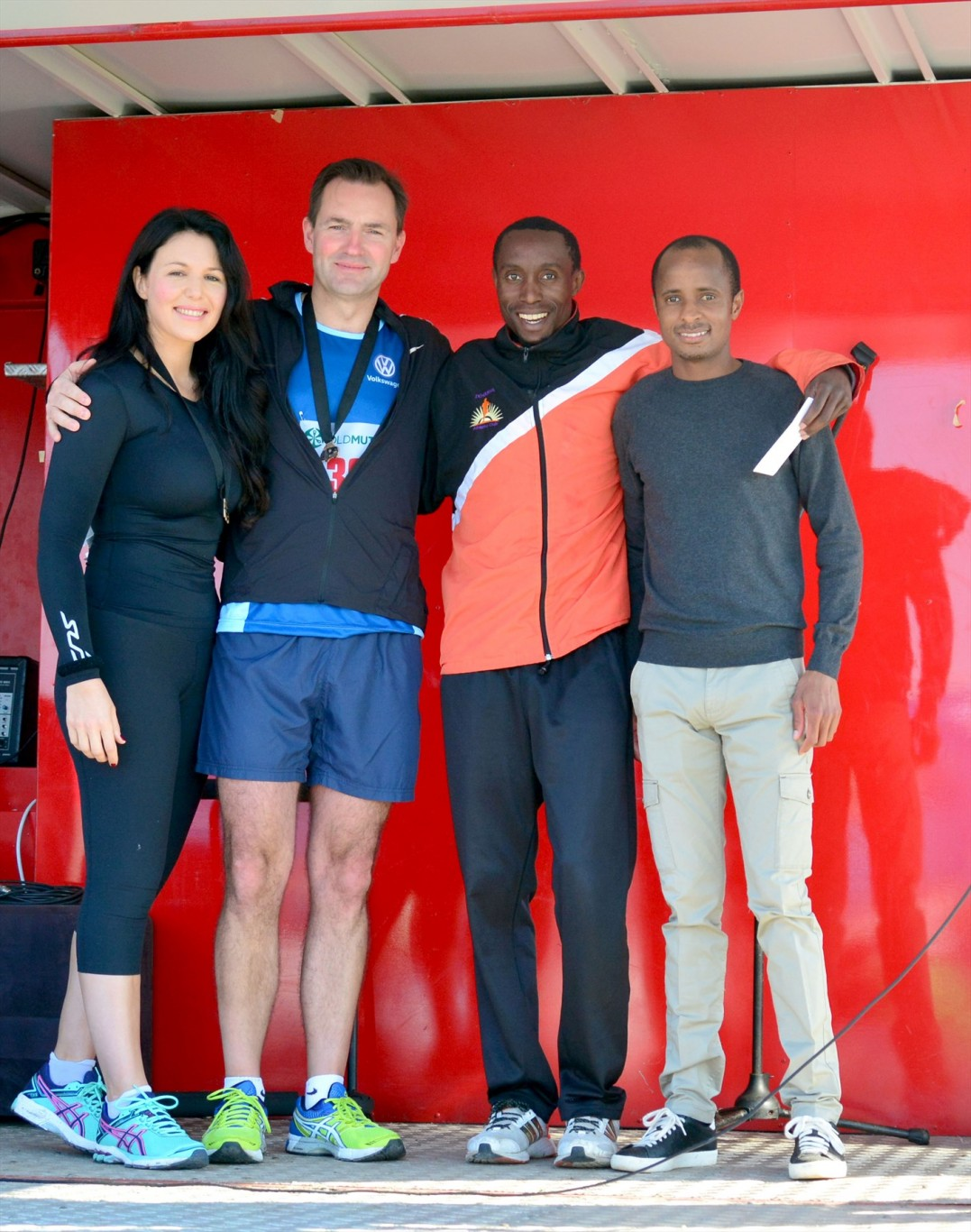 From L-R: Wendy Schaefer, who ran with her husband, Volkswagen Group South Africa Chairman and Managing Director, Thomas Schaefer with the winner of the Men's 10km race Amos Nyongo and SA Rio Olympics participant Lusapho April.