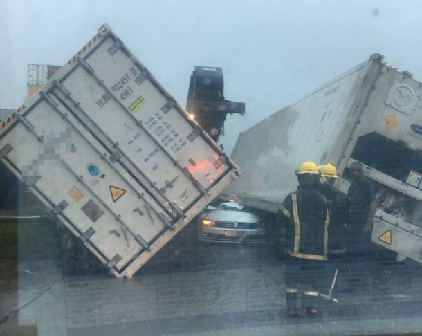 One killed and one injured after shipping containers fell on vehicle